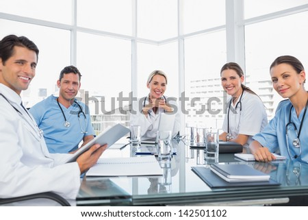 Smiling medical team during a meeting looking to the camera - stock photo