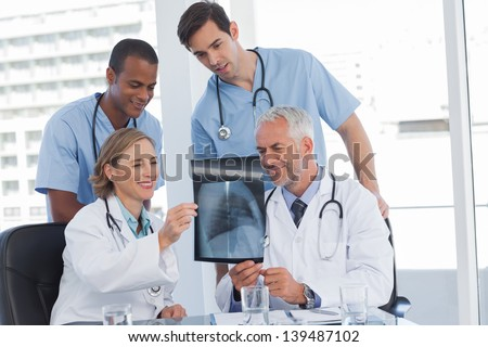 Smiling medical team examining radiography in bright office - stock photo