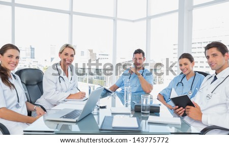 Smiling medical team in a bright meeting room - stock photo