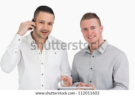 Smiling men holding a phone and a tablet computer against a white background - stock photo