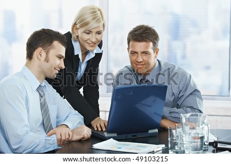 Smiling mid-adult businesspeople at meeting looking at laptop in office. - stock photo