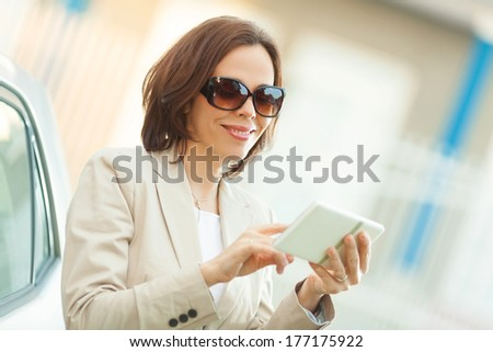 Smiling mid adult businesswoman using digital tablet outdoors. - stock photo