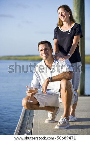 Smiling mid-adult couple relaxing with drink on dock by water