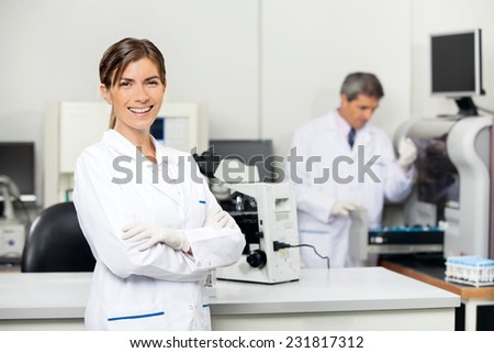Smiling mid adult female scientist with colleague working in background at medical laboratory - stock photo
