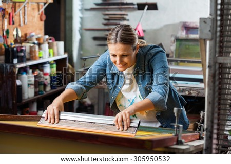 Smiling mid adult female worker using squeegee in factory - stock photo