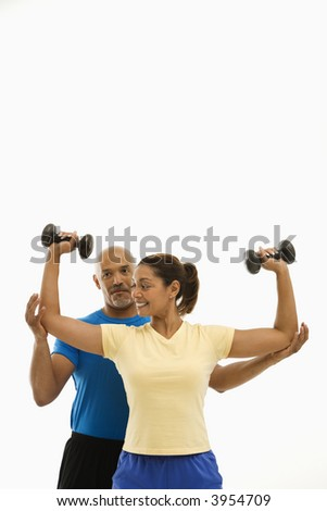 Smiling mid adult multiethnic man assisting mid adult multiethnic woman with dumbbells.