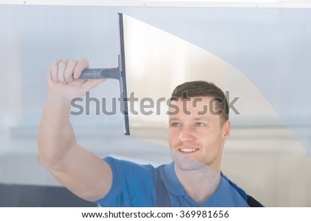 Smiling mid adult worker cleaning glass window with squeegee