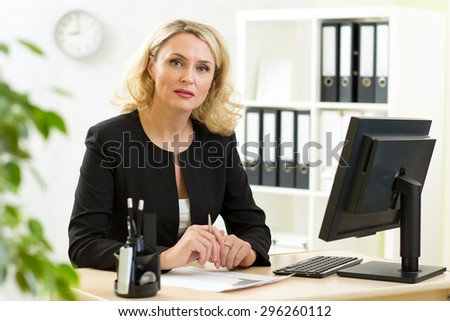 Smiling middle-aged business lady working in office - stock photo