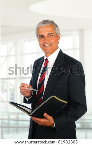 Smiling middle aged businessman holding a binder and his eye glasses while standing in an office lobby. - stock photo