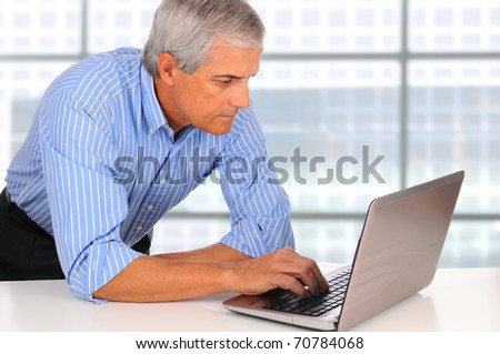 Smiling Middle Aged Businessman leaning on desk using laptop computer with large window background - stock photo