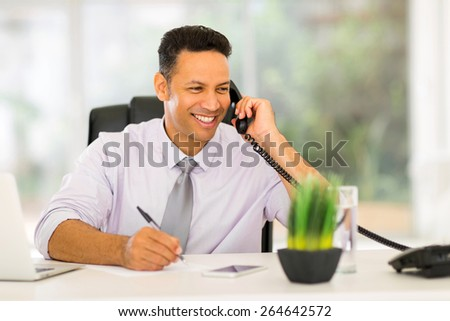 smiling middle aged businessman talking on landline phone and writing report - stock photo