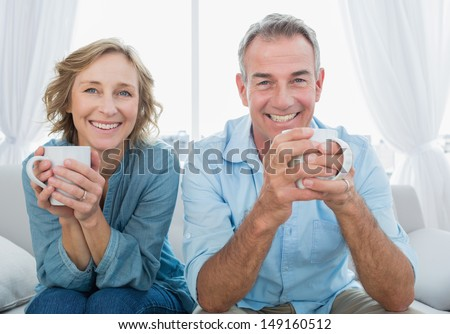 Smiling middle aged couple sitting on the couch having coffee looking at camera at home in the living room - stock photo