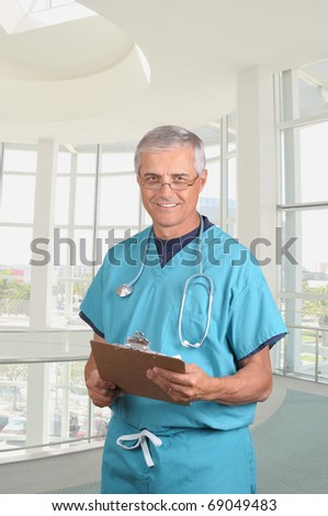 Smiling middle aged doctor in scrubs holding a patients cart on his clipboard. Vertical composition in modern medical facility. - stock photo