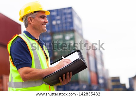smiling middle aged harbor worker at container depot - stock photo