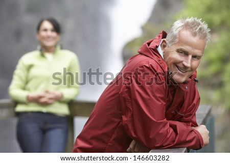 Smiling middle aged man with blurred woman in the background against waterfall - stock photo