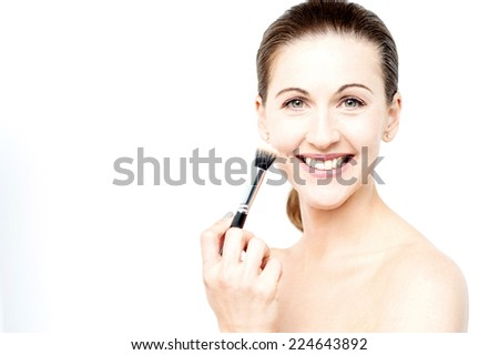 Smiling middle aged woman applying makeup on her face