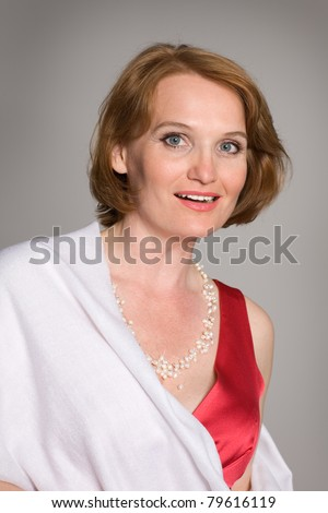 Smiling middle aged woman in a red dress with pearls. - stock photo