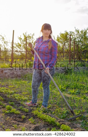 Smiling middle-aged woman leaning on her rake as she works in the vegetable garden in evening light holding a blue plastic watering can