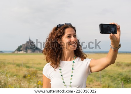 Smiling middle aged woman taking a selfie with mobile phone outdoors in front of Mont Saint Michel. France. - stock photo