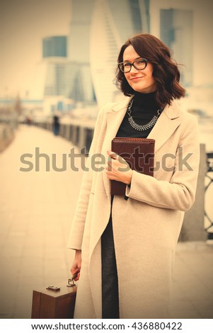 smiling middle-aged woman with glasses on his face, with books and wooden case in their hands on open air. instagram image filter retro style - stock photo