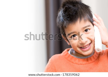 Smiling mischievous little boy making a telephone call indoors looking at the camera with a cheeky grin, with copyspace to the left - stock photo