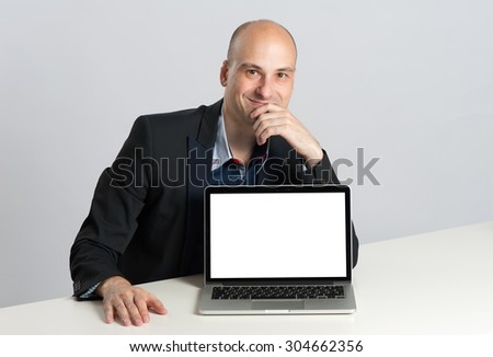 Smiling modern businessman sitting at office desk and showing laptop with blank screen - stock photo