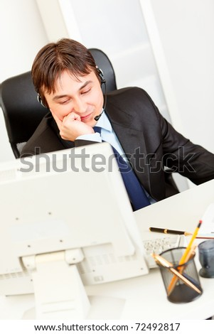 Smiling modern businessman sitting at office desk and talking on headset