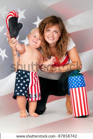 Smiling mom and son waving his hand on American flag background. Boy in boxer shorts with  boxing gloves and pear - stock photo