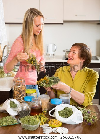 Smiling mother and adult daughter at the table with herbal tea and herbs