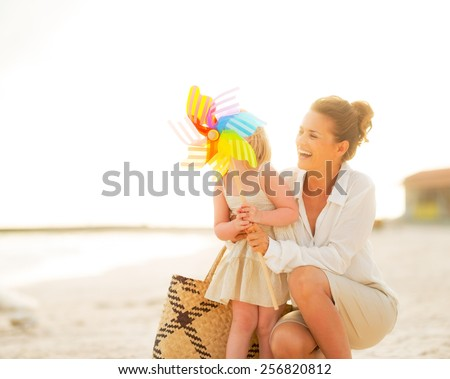 Smiling mother and baby girl behind colorful windmill toy on beach at the evening - stock photo