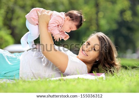 Smiling mother and baby girl enjoying in a park