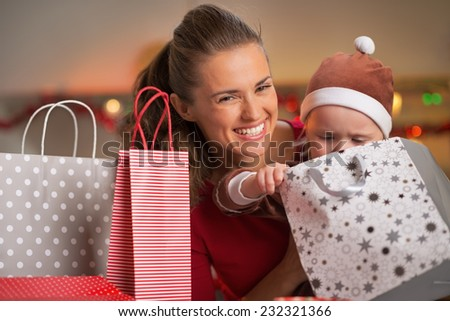 Smiling mother and baby looking in christmas shopping bag - stock photo