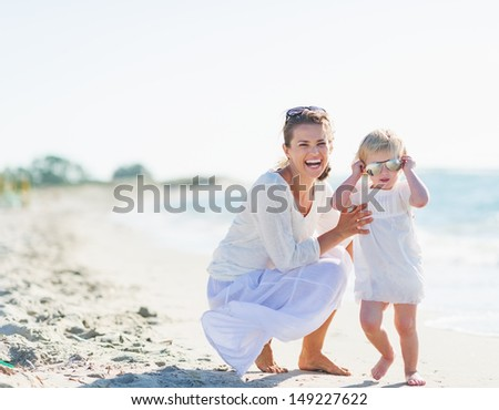 Smiling mother and baby wearing sunglasses on beach - stock photo