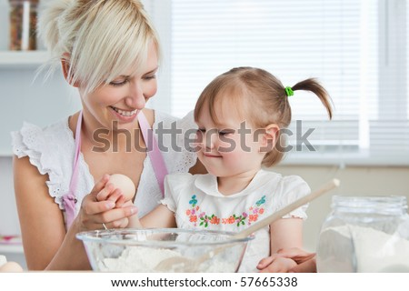 Smiling mother and child baking cookies in kitchen - stock photo