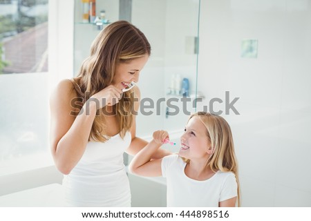 Smiling mother and daughter brushing teeth at home - stock photo