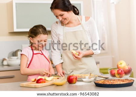 Smiling mother and daughter cutting apples for baking a pie - stock photo