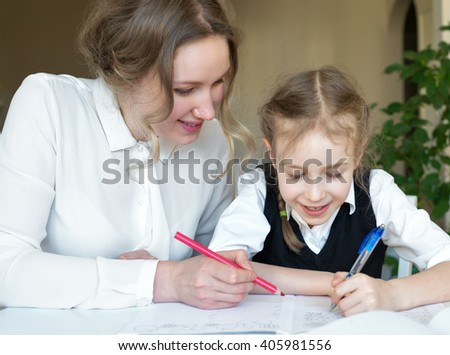 Smiling mother and daughter doing homework at home.
