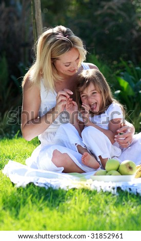 Smiling mother and daughter having fun in a picnic - stock photo
