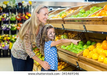 Smiling mother and daughter in grocery shop - stock photo