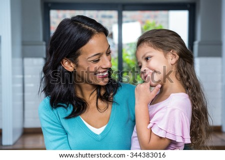 Smiling mother and daughter in living room at home