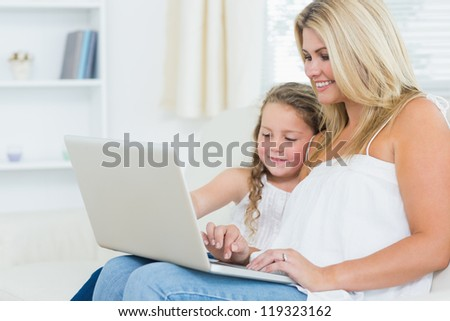 Smiling mother and daughter on the laptop in the living room