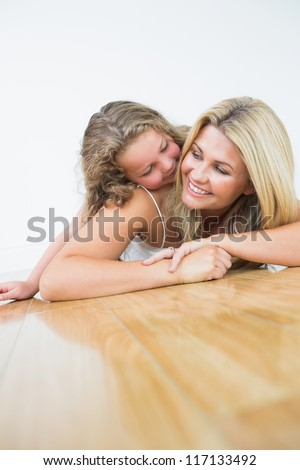 Smiling mother and daughter on the wooden floor - stock photo