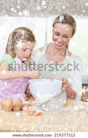 Smiling mother and daughter preparing dough for cookies against snow falling - stock photo