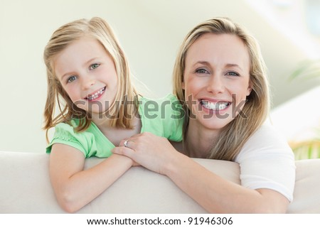Smiling mother and daughter together on the sofa - stock photo