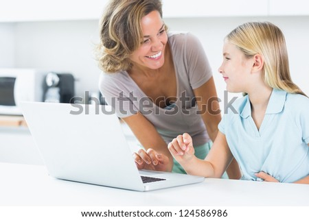 Smiling mother and daughter with laptop in the kitchen