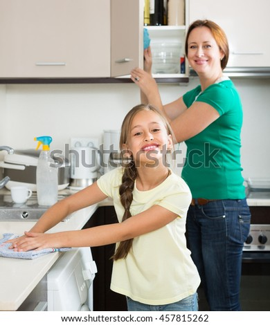 Smiling mother and happy playful daughter cleaning together at home kitchen. Focus on girl - stock photo