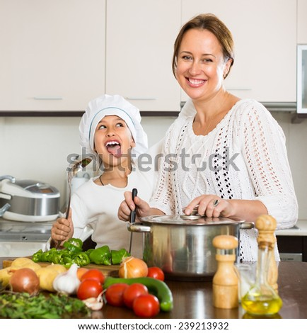 Smiling mother and her cheerful daughter preparing soup at domestic kitchen. Focus on girl - stock photo