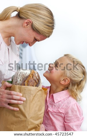 Smiling mother and her daughter unpacking grocery bag in the kitchen - stock photo