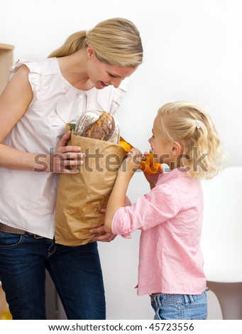 Smiling mother and her Little girl unpacking grocery bag in the kitchen - stock photo
