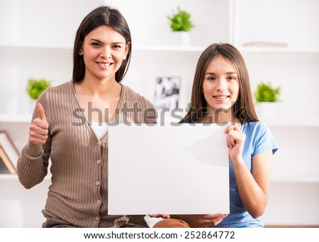 Smiling mother and her teen daughter are holding a white blank and looking at the camera. - stock photo